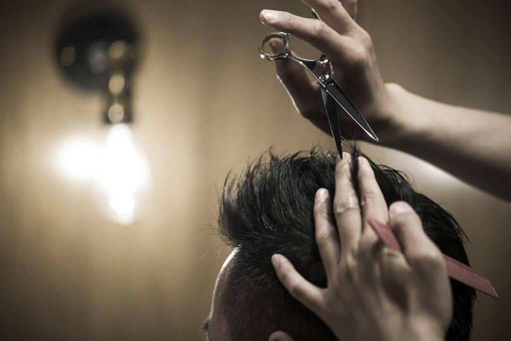 ハサミで髪をカットする美容師の手
